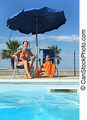 young mother in orange bikini and daughter sitting on beach...