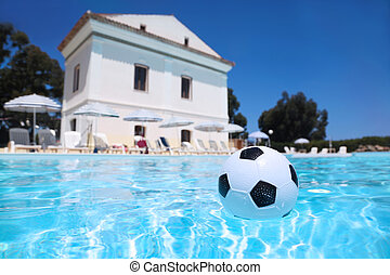 Soccer ball lies in water in day-time in pool under...