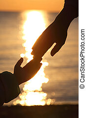 Silhouettes of two hands of child and  grown man adjoin fingers in evening at seaside during sunset