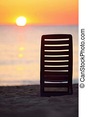 Dark blue plastic chair stands on beach near sea during...