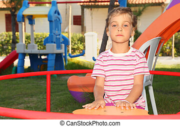 serious little girl in pink shirt sitting on merry-go-round...