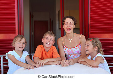 Woman with three children sits in number on verandah table...