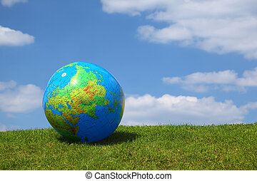 Large inflatable globe lies on grass in day-time