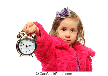 Little glamour girl in pink coat shows time on round alarm clock