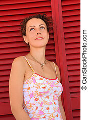 Woman stand near door from red horizontal jalousies and...