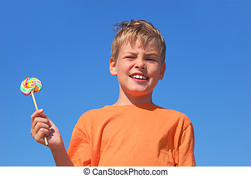 little boy in orange shirt holding multicolored lollipop,...