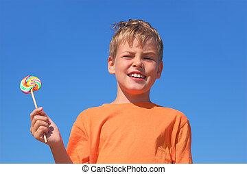 little boy in orange shirt holding multicolored lollipop,...