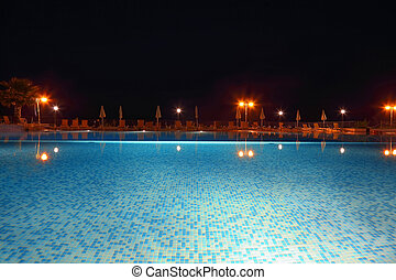 In  evening pool under open-skies which is lighted up lanterns