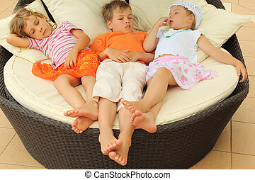 two tired little girls and boy lying on big circle armchair...