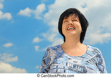 brunette plumpy mature woman smiling, blue sky and clouds