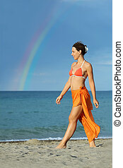 young brunette woman in orange bikini and pareo walking on...