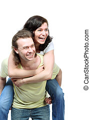 Happy young couple in jeans, funny girl jumps on boyfriend...