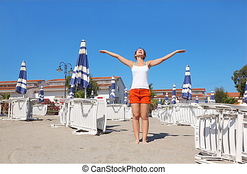 young woman in white shirt standing on beach near lounges...
