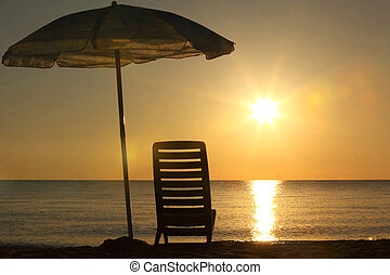 One plastic chair stands on beach under opened umbrella on...