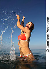 Young beautiful woman wearing red bathing suit spinning in sea. many drops