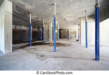 Blue support for concrete ceiling inside unfinished building