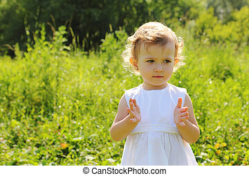 Little girl standing in the grass shows something with her...
