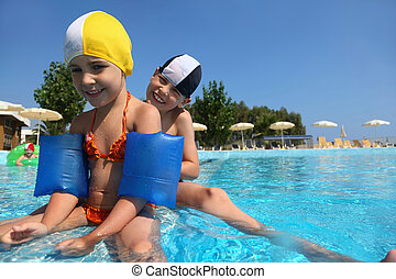 Three children play in day-time in large pool under...