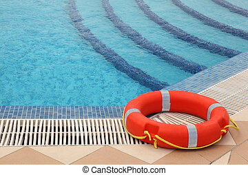 red lifebuoy with yellow ropes on tiled floor near swimming...