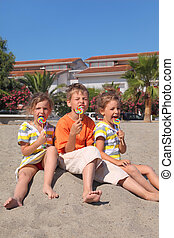 little boy and two girls sitting on beach and eating...