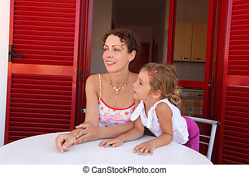 Daughter and mother sit on verandah round table near door...