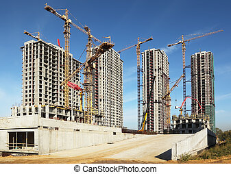 Four tall buildings under construction with cranes against a...