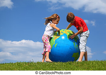 Brother with  sister stand on  grass and study  map on an inflatable globe