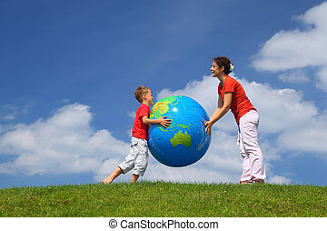 Mother with son play an inflatable globe in day-time stand...
