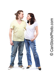 Young couple in jeans, boy and girl, are standing in embrace and looking at each other
