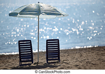 Two dark blue empty chairs stand on beach near sea under...