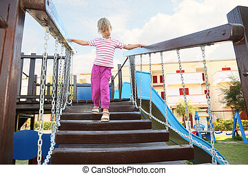 little girl standing on suspension bridge on playground,...