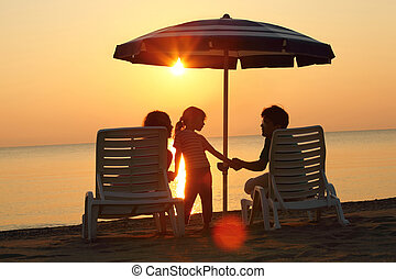 Mother and father sit on  beach in  evening under  umbrella and hold daughter on hands