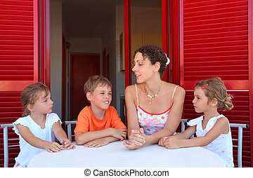 Three children and mother sit on verandah round table near...