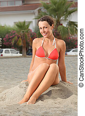 young woman in orange bikini sitting on beach and smiling,...