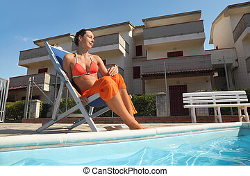 young woman in orange bikini and pareo sitting on beach chair near pool with closed eyes and smiling, house