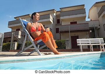 young woman in orange bikini and pareo sitting on beach...