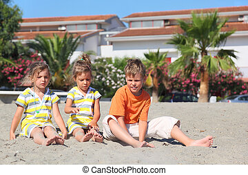 little boy and two girls sitting on beach, palms and...