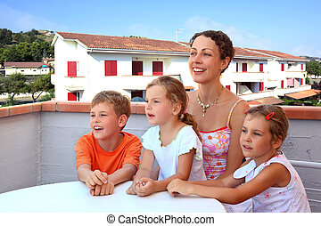 Mother and three children sit in day-time on balcony near...