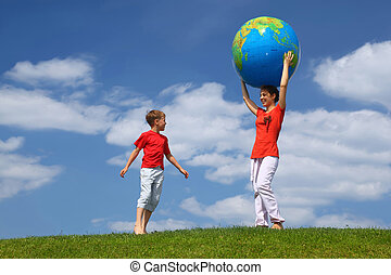 Mother stands on grass and holds hands large inflatable ball...