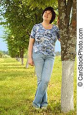 plumpy brunette woman standing on lawn near tree, smiling...
