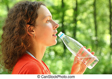 Woman drinks water from  bottle and looks frontwards
