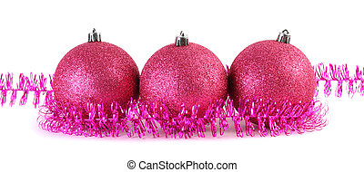 Three red Christmas tree balls surrounded by purple tinsel lies in the range