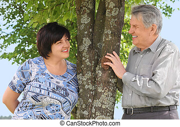 old senior and his adult daughter standing near tree and...