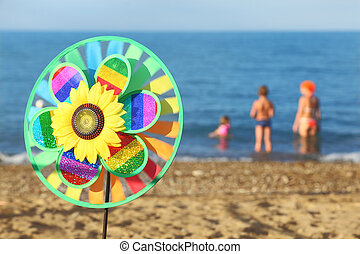 multicolored pinwheel toy with flower on beach, family...