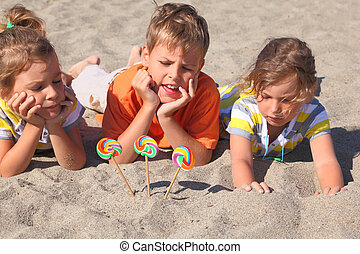 little boy and two girls lying on beach, chin on hands,...