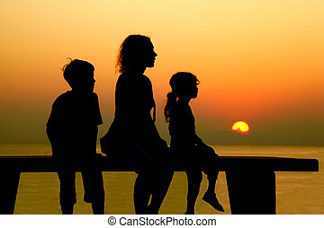 Mother with two children sits on bench and looks at beach...