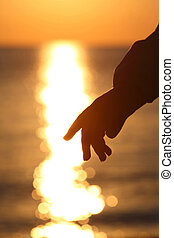 Silhouette of hand of child  and sun way on salt water