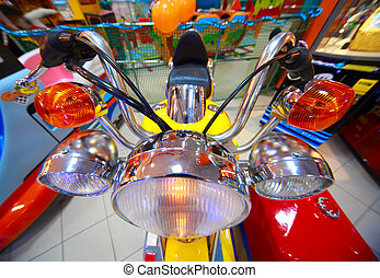 Close-up view of childish small yellow-red tricycle with headlights