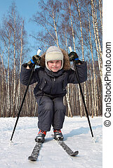 Young boy skates on cross-country skis inside winter forest...