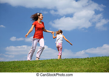 Mother with daughter hurry and play on grass in day-time